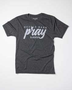 """On a heather charcoalwith """"Hustle Hard Pray Harder"""" design. FIT: Unisex - True to size. Size Bust/Chest Inches XS 30-32 Small 34-36 Medium 38-40 Large 42-44 X"""