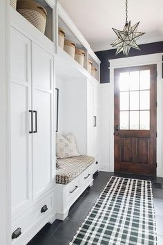 Positioned under shelves holding woven baskets, white closed lockers contrasted with oil rubbed bronze hardware and located on either side of a white built-in storage bench topped with a houndstooth cushion.
