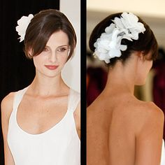 Classic French Twist Adorned with a Cascade of White Fabric Flowers, Off Center Part and Side Swept Bangs, Long Straight Hair.