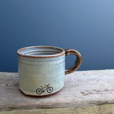 A medium sized mug with soft blue glaze and hand drawn mountain bike print.  It was thrown and hand modelled in my studio in rural Inverness