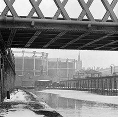 A stretch of the Regents Canal in St Pancras, Camden, looking south east under the now-demolished canal footbridge towards the gas towers of British Gas Station with the south east clock tower of St Pancras Station visible in the background. Camden London, Camden Town, Old London, Regents Canal, London Pictures, English Heritage, Canal Boat, Greater London, Historical Pictures