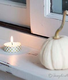 An easy and quick Fall decoration with mini pumpkins and votive lights decorated with washi tape on the ledge of a hutch. via http://www.songbirdblog.com