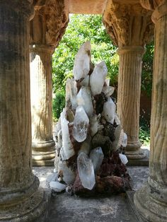 magnificent quartz crystal cluster placed in the center of grand old stone columns / Mineral Friends