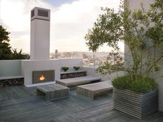 The roof deck at this modern San Francisco home features an expansive panorama of the city skyline as well as a welcoming fireplace.
