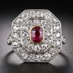 Edwardian platinum over 18K yellow gold ring featuring a .50 carat antique cushion cut ruby sweetened by two rows of old mine cut diamonds (1.75 carats total weight, H-J color, VS-SI clarity) radiating out in an octagonal shape and set into the pierced shoulders.