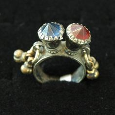 17th Century Holy Lands Brass ring features a two prong setting with a intact faceted red and blue glass stones. This ring also has small loops with adornments on each side of the setting. These loops were designed to allow the woman to connect this ring to other rings, bracelets and are bands with small chains. Ring size 8.25, sizing not recommended.