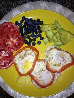 Eggs fried inside a red pepper, tomatoes, blueberries, avocado