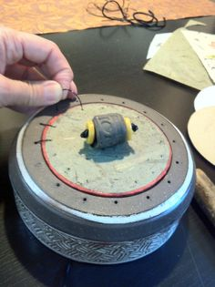 Making a lid. 'Sewing the paper lid to the clay lid. Handmade bead on top