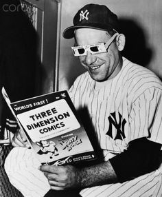 Yogi Berra of the New York Yankees, a longtime enthusiast of comic magazines, seems particularly pleased with a new type of funny book given him by the Madison Square Boys Club. Yogi donned a pair of 3-D glasses and took time in the dressing room to catch up on his reading.