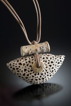 Pendant   Nina Morrow. Driftwood, shaped, with burnt design,bone bead and strung on cotton cord