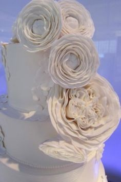 Lots of texture going on in this cake.  Sugar ranunculus and patience roses spill over the top and five-petal blossoms overlap in sections for an extra layer on top of the buttercream.