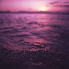 Mediterranean sea water off Ibiza Spain in surreal purple sunset evening dusk colors film analog photo