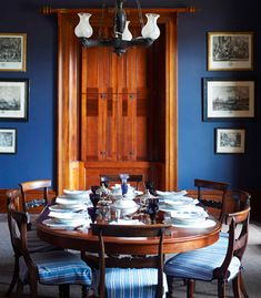 A traditional dining room in royal blue. Late Regency tables and chairs.