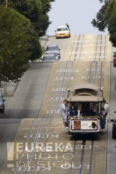Cable car filled with tourists on vacation making its way along a steep section of Powell Street in San Francisco, California.