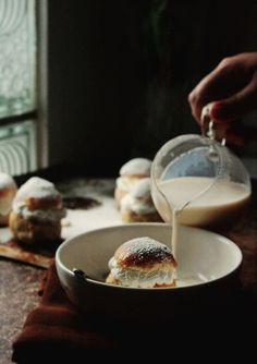 Semlor, Sweden | sweet cardamon buns with whipped cream, served in a bowl with hot milk