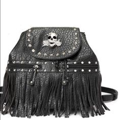 Skull & Roses Black Backpack Brand new with tags. Convertible purse backpack. Pebbled vegan leather with fringe and studs. Adorned with silver skull with roses. 13 X 10 X 7. Four metal feet on bottom. Adjustable, removable straps, back zipper pocket, two front zipper pockets and inside back wall zipper pocket.Please ask all your questions before you purchase! I am happy to help! Sorry, no trades. Please, no lowball offers. Happy Poshing! Blue Heaven Bags Backpacks