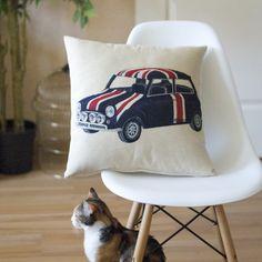 Un coussin de la collection Authentiques sur une jolie chaise Eames.