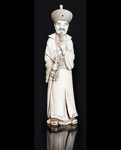 Japan, c. 1900. Ivory, carved and with partly tinted decoration. Standing figure wearing characteristical garment. Lab. 'Dai Qing'. H. 25 cm.