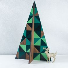 This on-trend geometric wood Christmas tree decoration makes the perfect centrepiece or acts as an alternative tree to put gifts under. The tree is made up of two sides which slot together easily to form a 4D wooden shape. Printed with festive greens and teals, the tree can also be bought as a set with a smaller pale version.