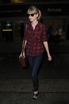 Taylor Swift looks to be wearing bowling shoes as she lands into rainy LA! The country singer touched down from Sydney, Australia wearing a red chequed shirt and jeans with the unusual footwear. Taylor was whisked off quickly into a waiting limo out of LAX. #airport #celebrity #style #fashion #looks #travel
