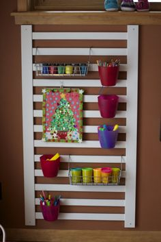 Art materials are being stored in hanging containers on this repurposed crib rail. Everything has a place!