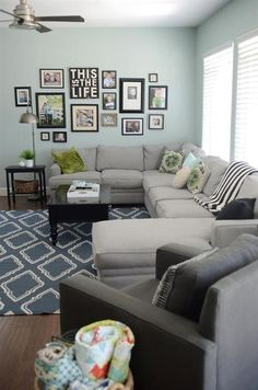 I love this grey sectional coch with the black coffee table! The green throw pillows are great accents to this living room.