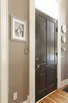 Greige walls, white trim, black door, wood floors