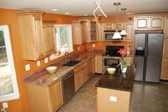 Granite countertops orange walls, stainless steel fridge?
