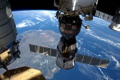 Docked Soyuz spacecraft in center of frame with Cygnus cargo craft at left and Progress craft at right with Earth below