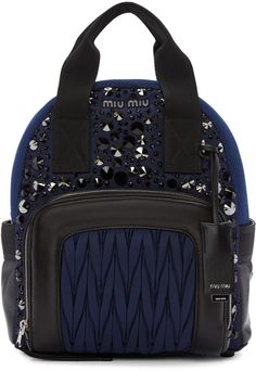 Textile backpack in blue. Buffed leather and mesh trim in black throughout. Twin carry handles. Adjustable shoulder straps. Crystal-cut stud embellishments, logo plaque, covered pocket mirror on detachable lanyard, and zippered compartment featuring ruched quilted detailing at face. Patch pocket with logo embroidered band at sides. Two-way zip closure at main compartment. Zippered pocket, patch pocket, and logo plaque at interior. Textile lining in black. Silver-tone hardware. Tonal…