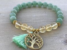 Prosperity Bracelet, Aventurine, Citrine This beautiful bracelet is made of 8mm Aventurine beads, 8mm Citrine beads, gold spacers, gold rhinestones, and it is adorned with a tree of life pendant and a mini 20mm tassel. The bracelet shown fits to 7.75 inches wrist but you can
