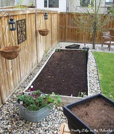 Stones around raised garden beds and baskets hanging from the fence. Love this idea for a vegetable garden. raised beds fence, backyard planter ideas, stone garden beds, garden beds along fence, backyard gardens, vegetable gardening ideas, raised gardens ideas, raised garden beds, backyard edging ideas
