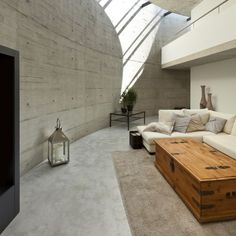 Wände und Boden aus Sichtbeton und weiche Couch in Beige