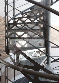 Photo DH88 - SPIR'DÉCO® San Francisco. Escalier hélicoïdal d'intérieur sur 2 niveaux en acier au design industriel pour une décoration de caractère. Marches Nanoacoustic® tôle striée pour un escalier tout métal silencieux. Contremarches et limon découpés façon charpente à l'ancienne avec rivets forgés. Finition : acier brut patiné. - Modèle déposé - © Photo : Nicolas GRANDMAISON