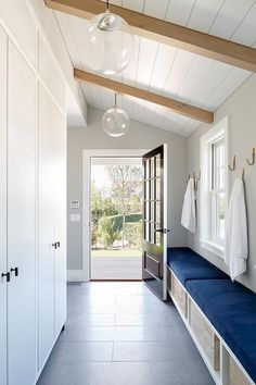 White and blue mudroom features long side-by-side storage benches filled with woven bins topped with cobalt blue velvet cushions placed under brass hooks placed under a sloped shiplap ceiling.