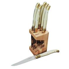 Six handmade stainless steel steak knives with ivory-finished handles and a block holder. Made in France.  Would be awesome in a gold or white marble block...