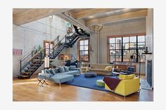 So industrial, yet comfortable. Love the furniture pieces. Makes me want to walk up those stairs and see what's up there