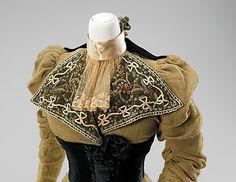 1896-99  Material: lana, seda.   Este incorpora una buena combinación de satén mate junto lana para crear un vestido de día memorable e impactante. La valentía de las solapas grandes y cintura son indicativos de refinado diseño y el estilo elevado de mano de obra de alta costura. Las hermanas Fox eran diseñadoras exclusivo