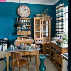 Une cuisine ancienne à la déco très sommaire devient une pièce à l'esprit brocante, à la fois urbaine et moderne, grâce à une peinture bleu canard et des meubles un brin rustiques et industriels.