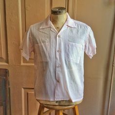 For your consideration we have a really fun vintage shirt from the 1950s. Done in a pale pink puckered nylon, this shirt features loop collar
