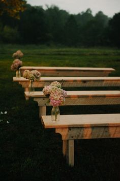 Simple outdoor wedding ceremony decorations ideas. Long wooden benches with vases & flowers on the ends.