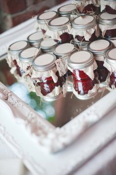 Small jars of preserves dressed up as wedding favors.