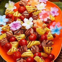 Serve finger food like ham-and-pineapple kabobs at the luau. Embellish plain wooden skewers by gluing Hawaiian flower petals to one end.