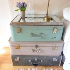 painted or fabric/mod podged suit cases, stacked, mirror on top. cute and multifunctional night stand.