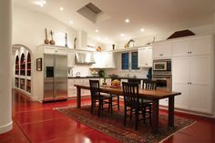 The bold color of the red stained concrete floors against the clean white walls and cabinets create a perfect backdrop.  Art, love, and passion for life is what drove this project.