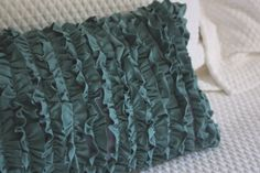 DIY ruffle pillow using old shirts.  The actual case was made with an old men's dress shirt so that the pillow closes in the back by buttoning and unbuttoning the shirt.... Cool idea!
