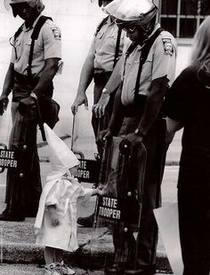 Here is a Georgia State Trooper in riot gear at a KKK protest in a north Georgia city back in the 80s. The Trooper is black. Standing in front of him and touching his shield is a curious little boy dressed in a Klan hood and robe. I have stared at this picture and wondered what must have been going through that Trooper's mind. Before the Trooper is an innocent child who is being taught to hate him because of the color of his skin