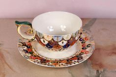 The tea pair Firebird is made of porcelain, painted with underglaze paints, overglaze paints and lustrs. The details on the saucer and cup have plating. The main theme of the tea couple is a fairy bird from Russian folk tales, whose plumage impressed the imagination. For the decor, we took
