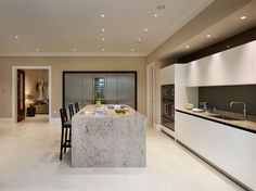 50mm granite worktop is used to create a monoblock style island with a barchair seating arrangement, Gaggenau induction hob and downdraft extractor.