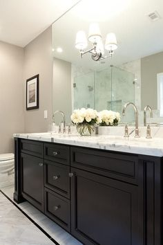 Welcoming bathroom boats a black dual vanity adorning glass knobs and a white marble countertop fitted with sink paired with polished nickel gooseneck faucets positioned in front of a frameless vanity mirror lit by a mirror mounted Restoration Hardware Wilshire Double Sconce.